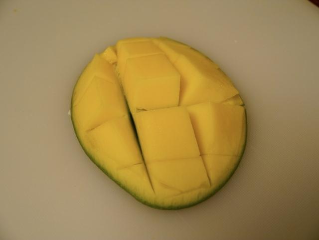 Jeg skjærer ruter i mangoen, vrenger den og skjærer lett av fine terninger